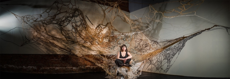 In the corner of a large gallery, a woven rope sculpture extends from a chair. The sculpture is attached to the ceiling and walls, resembling lines and forms of a crudely woven web. The artist, a small white woman with short black hair and a black jumpsuit, sit cross-legged in the chair.