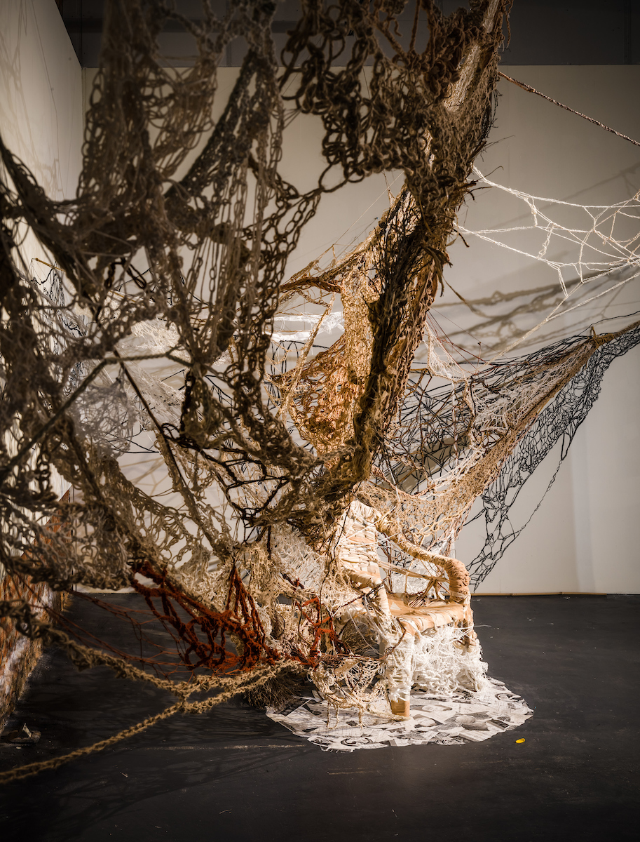 side view of a woven twine/burlap textile sculpture expanding from a plastic chair.